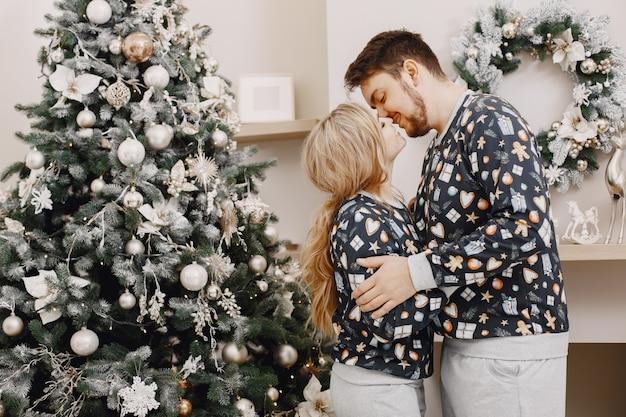 Personas en decoraciones de christman. hombre y mujer en pijama identifical. familia en casa.