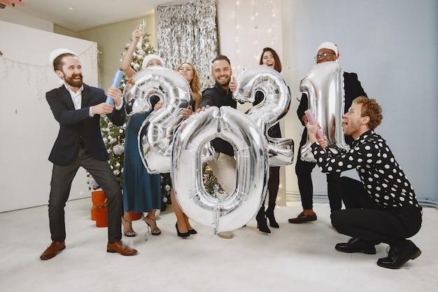 Personas en decoraciones de christman. hombre con traje negro. celebraciones grupales año nuevo. personas con globos 2021.