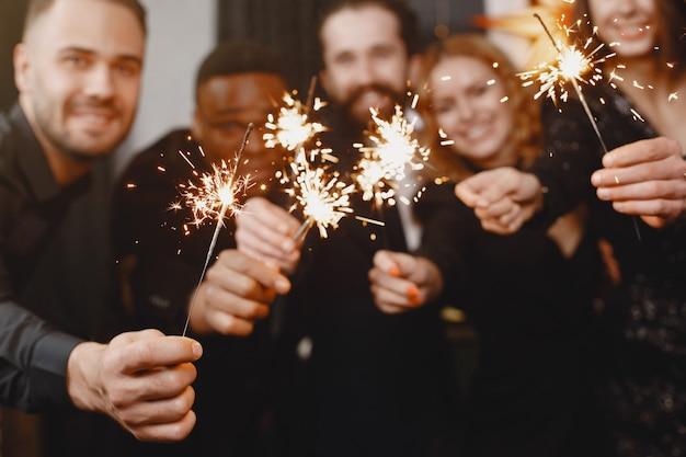 Personas en decoraciones de christman. hombre con traje negro. celebraciones grupales año nuevo. personas con luces de bengala.