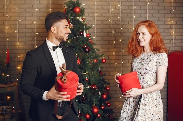 Personas en decoraciones de christman. hombre con traje negro. mujer con caja roja.