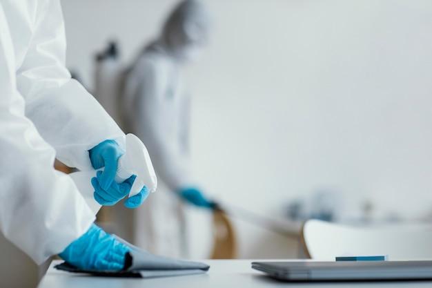Personas desinfectando un área de riesgo biológico