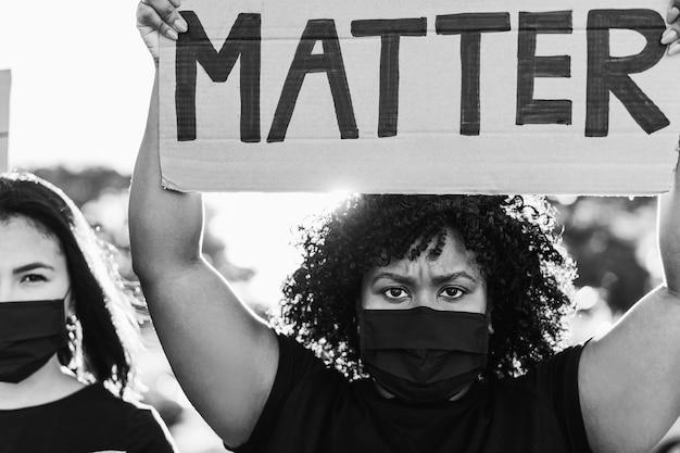 Personas de diferentes culturas y razas protestan en la calle por la igualdad de derechos - manifestantes con máscaras faciales durante la campaña de lucha contra las vidas negras - enfoque en la cara de niña negra