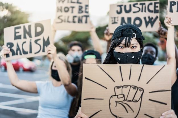 Personas de diferentes culturas y razas protestan en la calle por la igualdad de derechos con máscaras protectoras: enfoque en la niña asiática