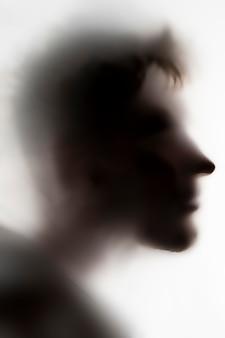 Las personas dirigen la sombra sobre un vidrio o superficie blanca, un fantasma terrible en una noche.