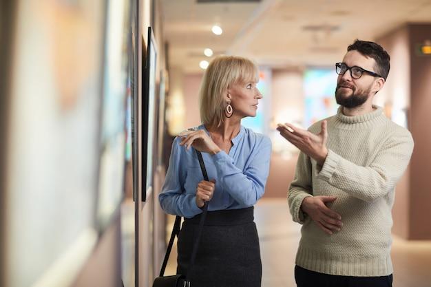 Personas discutiendo pinturas en la galería de arte