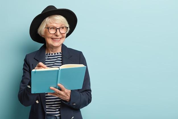 Personas, edad, concepto de tiempo libre. feliz mujer senior en pensión escribe lista para hacer en su bloc de notas azul