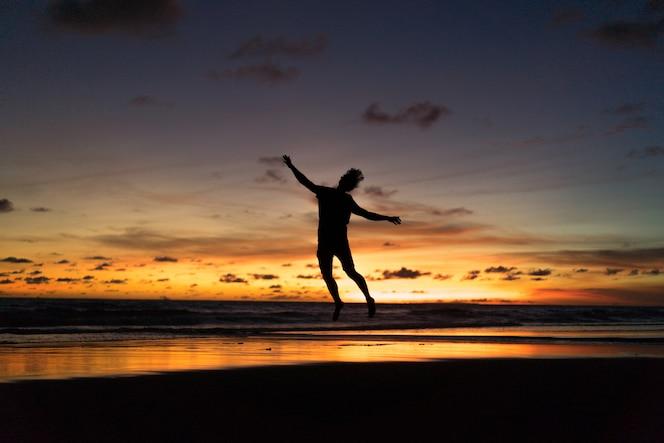 Personas en la orilla del océano al atardecer. hombre salta