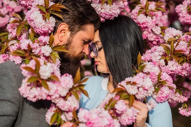 Personas enamoradas. pasarela romántica con flores de cerezo en japón. besos en el jardín de manzanos o cerezos en flor fresca. la pareja pasa tiempo en el jardín de primavera. felices pascuas. concepto de pareja cita romántica.