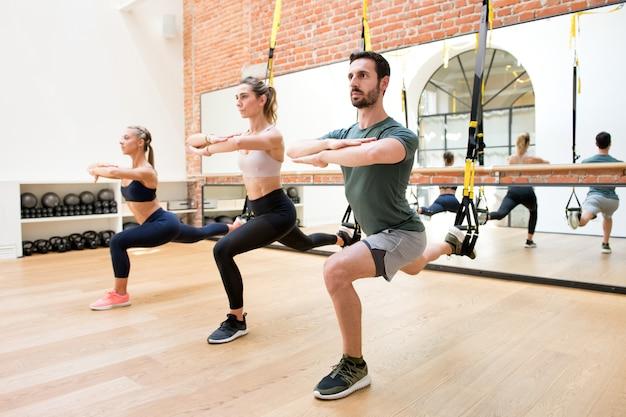 Personas entrenando piernas usando trx en el gimnasio