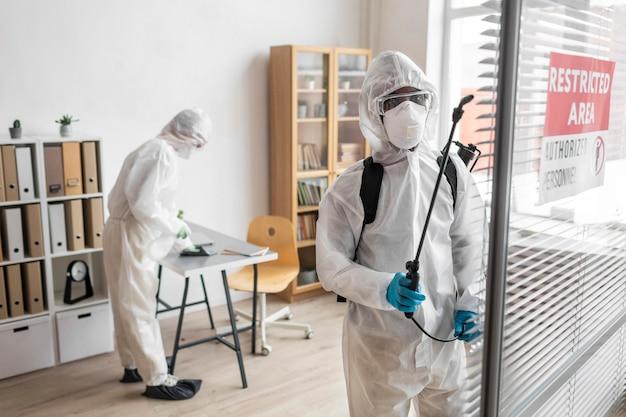 Personas con equipo de protección para desinfectar un área peligrosa