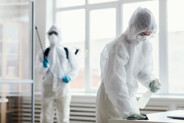 Personas en equipos de protección desinfectando