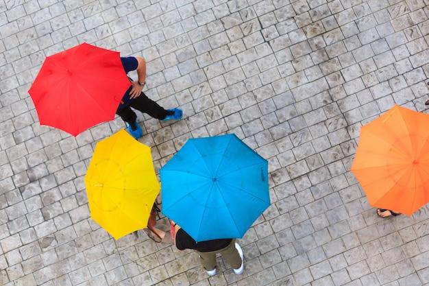Personas escondidas bajo el paraguas en un día lluvioso