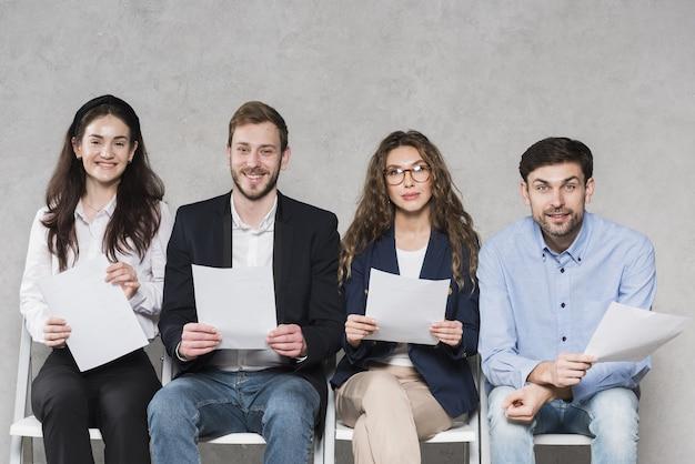 Personas esperando sus entrevistas de trabajo con currículums