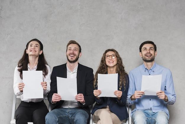 Personas esperando sus entrevistas de trabajo con papeles en blanco