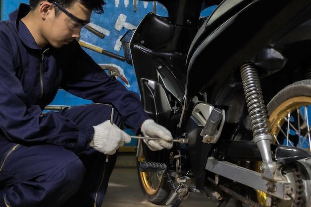 Las personas están reparando una motocicleta. use una llave y un destornillador para trabajar.