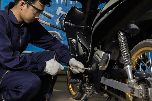 Las personas están reparando una motocicleta use una llave inglesa para trabajar.