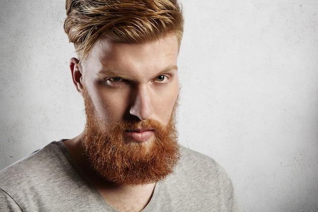 Personas y estilo de vida. foto de cabeza de guapo hipster con espesa barba roja y elegante cabello con expresión seria, entrecerrando los ojos.