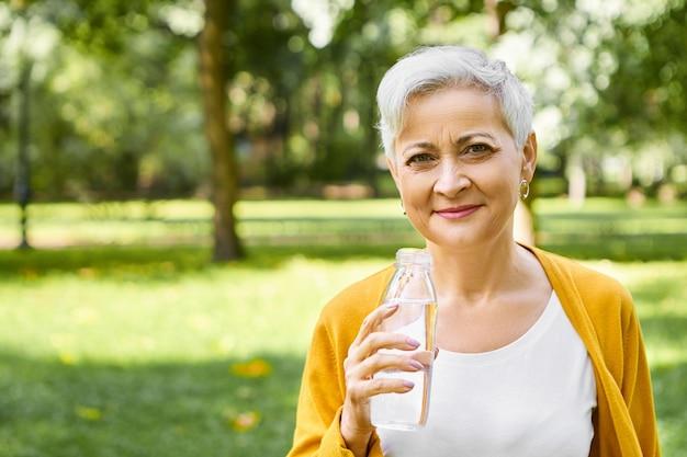 Personas, estilo de vida, hábitos saludables y concepto de refresco. imagen exterior de feliz enérgica anciana europea con corte de pelo corto sosteniendo una botella, disfrutando de agua potable en un día caluroso y soleado