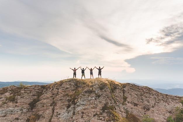 Personas exitosas con los brazos levantados en la cima de una montaña.