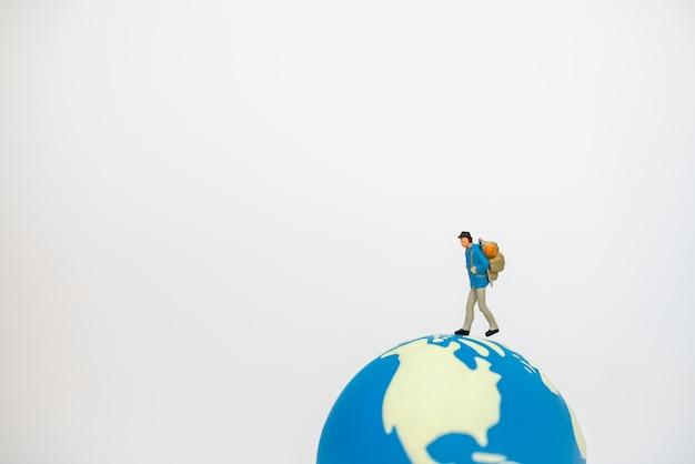 Personas de figura en miniatura de viajero con mochila caminando sobre la bola del mundo mini sobre fondo blanco.