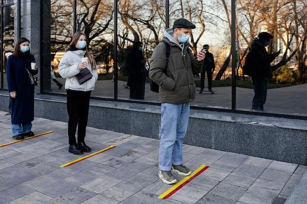 Personas en fila esperando detrás de la banda de distancia social.
