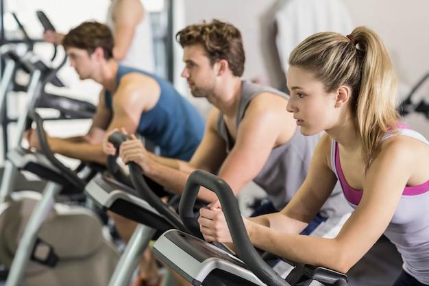 Personas en forma haciendo bicicleta de ejercicio en el gimnasio