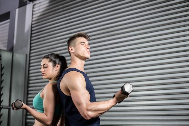 Personas en forma levantando pesas espalda con espalda en el gimnasio de crossfit