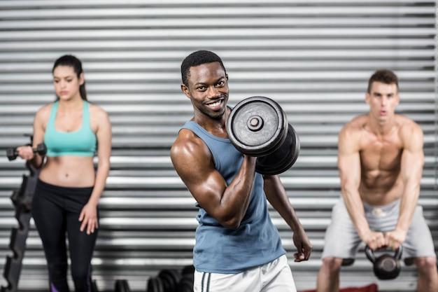 Personas en forma levantando pesas en el gimnasio de crossfit
