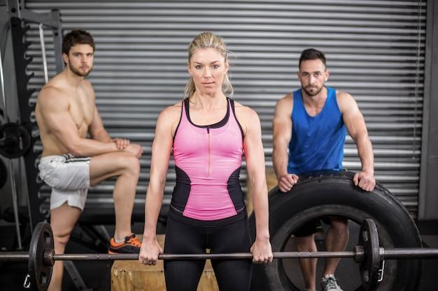Personas en forma posando con los pulgares para arriba en el gimnasio