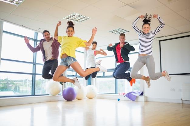 Personas en forma de saltar en la sala de ejercicios brillante