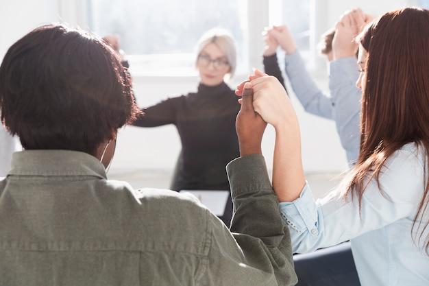 Personas formando un círculo y levantando las manos.