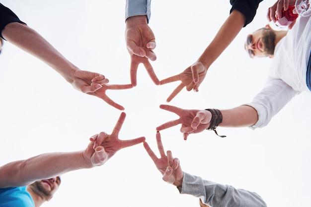 Personas formando forma de estrella con los dedos.