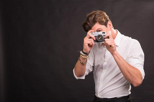 Personas, fotógrafo y concepto vintage: hombre que busca un tema interesante para su foto sosteniendo una cámara vintage en una pared marrón con espacio de copia