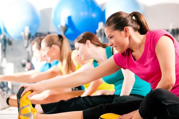 Personas en gimnasio calentando estiramientos
