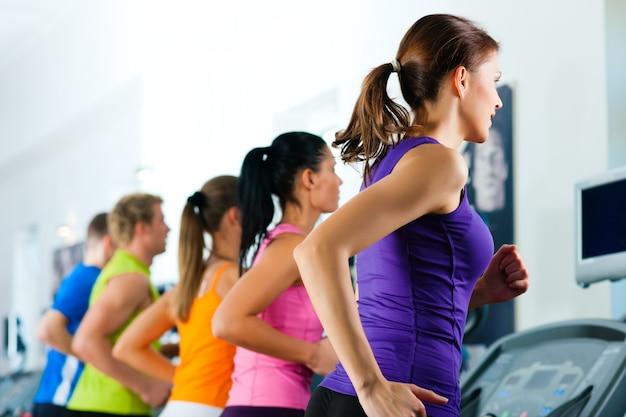 Personas en el gimnasio en cinta rodante corriendo