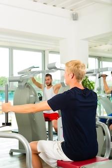 Personas en el gimnasio deportivo en la máquina de fitness