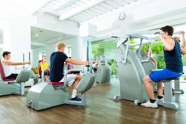 Personas en el gimnasio deportivo en máquinas