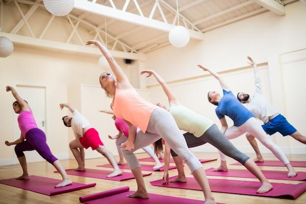 Personas en un gimnasio estirando un brazo hacia un lado