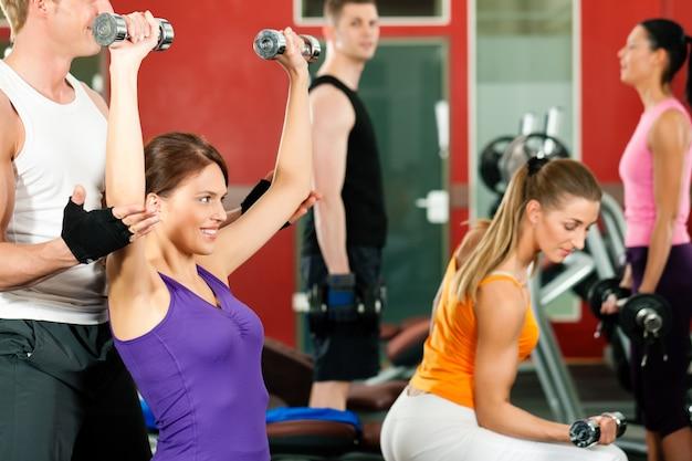 Personas en el gimnasio haciendo ejercicio con pesas