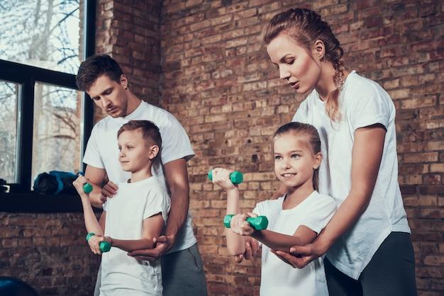 Personas en el gimnasio con mancuernas en camisetas blancas.