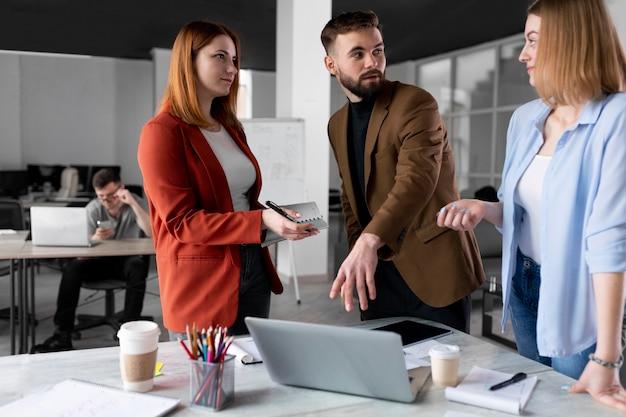Personas hablando en una reunión de grupo en el trabajo
