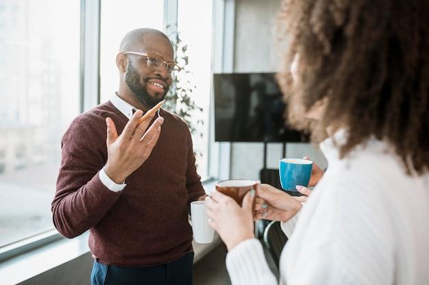 Personas hablando entre sí tomando un café durante una reunión