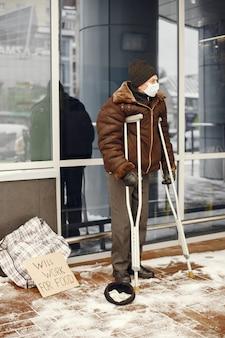 Personas sin hogar de pie cerca del edificio.