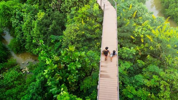 Personas del hombre y la niña en la vista superior a pie en el cielo de madera calzada en el bosque con árboles y el riv
