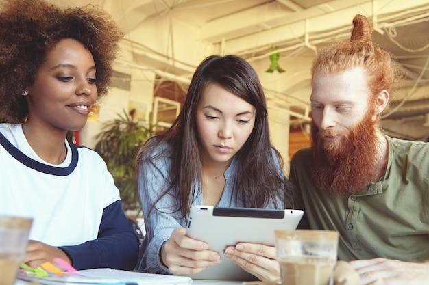 Personas, innovaciones y tecnología. los empresarios que estudian los datos financieros en la pc del panel táctil con mirada concentrada.
