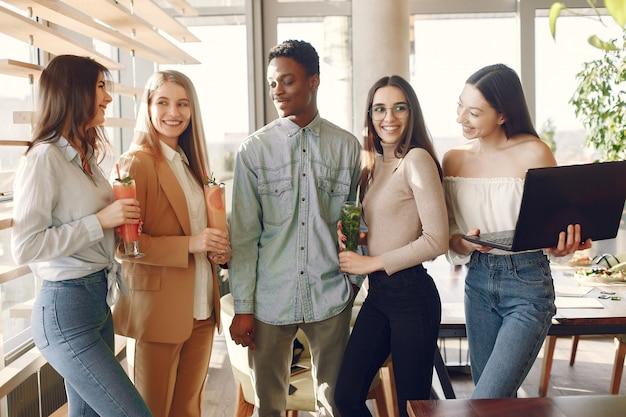Personas internacionales de pie en un café y bebiendo un cóctel.