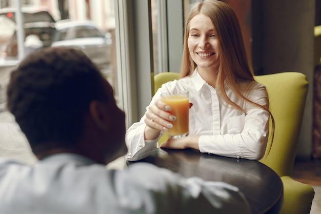 Personas internacionales de pie en un café y bebiendo un jugo