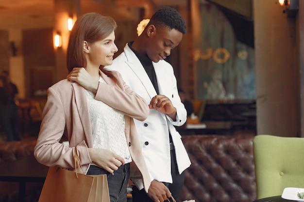 Personas internacionales de pie en una cafetería con bolsas de compras