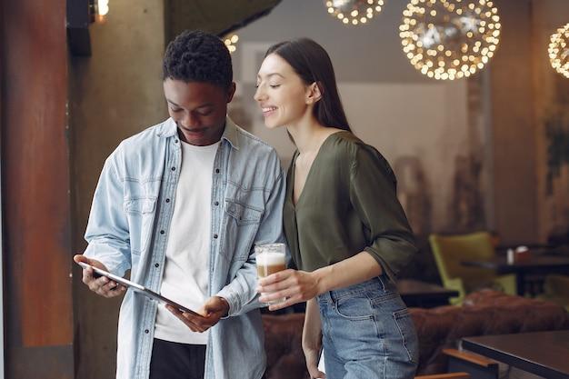 Personas internacionales de pie en una cafetería con tableta y café.