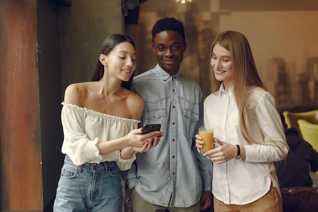Personas internacionales de pie en una cafetería con teléfono móvil